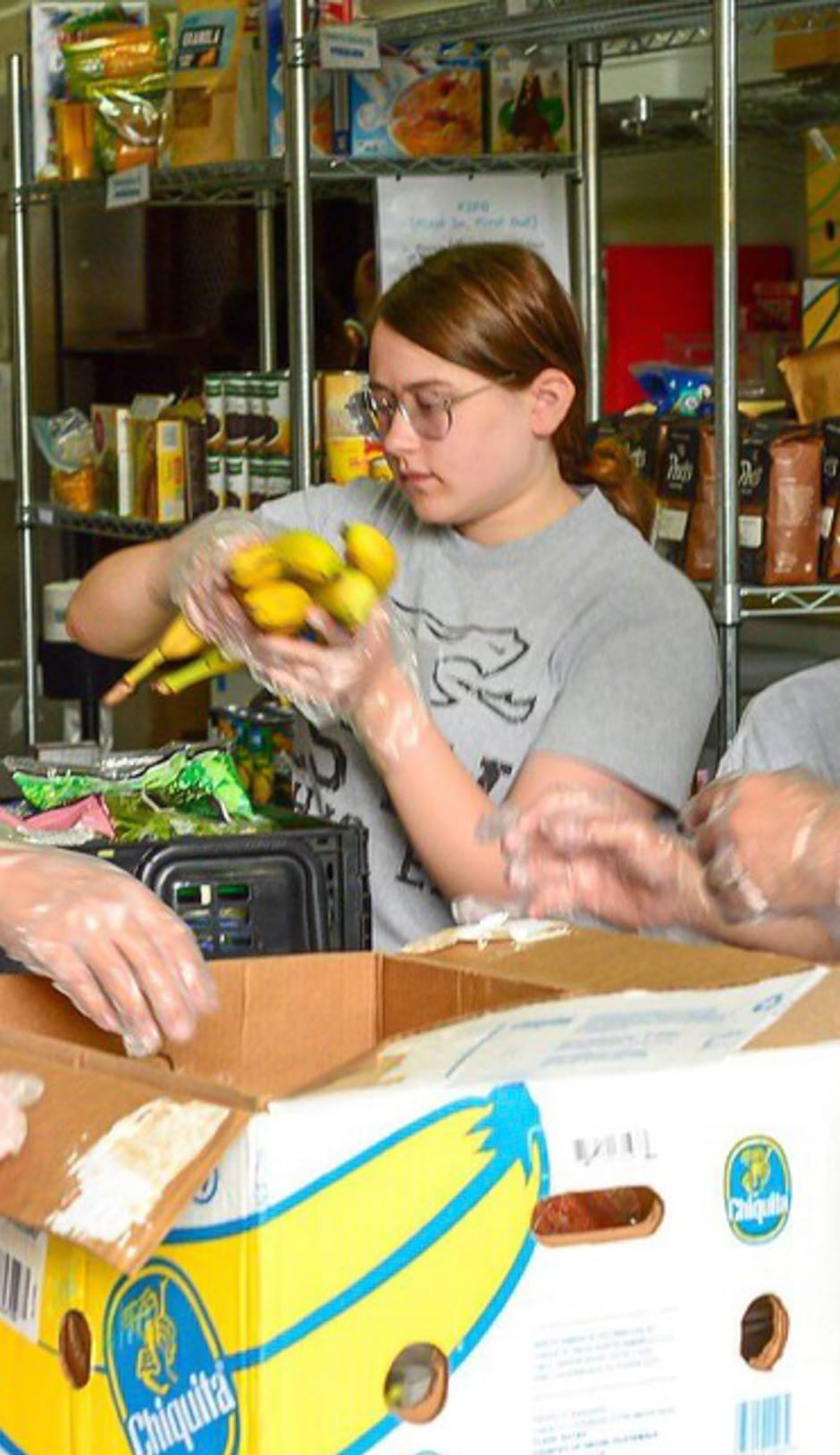 Girl sorting bananas and volunteering at a food bank for community service program