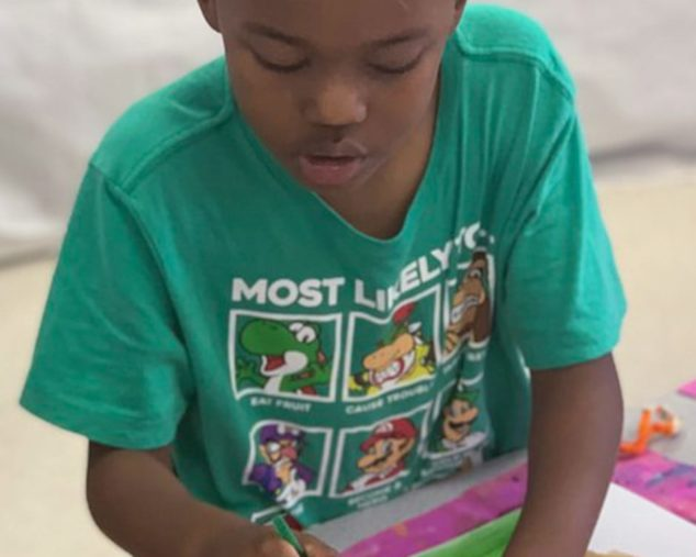 Boy painting during the Edge Afternoon program