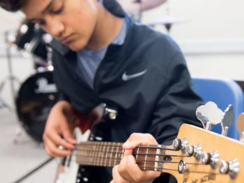 Older student playing guitar in the Rock Band program