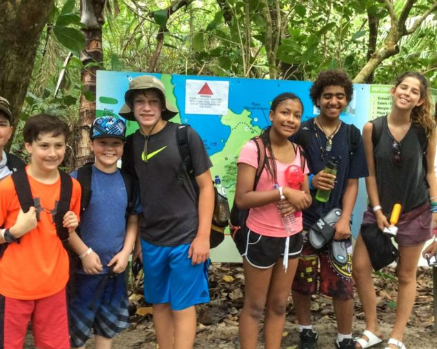 Group of kids standing in forest with hiking backpacks on