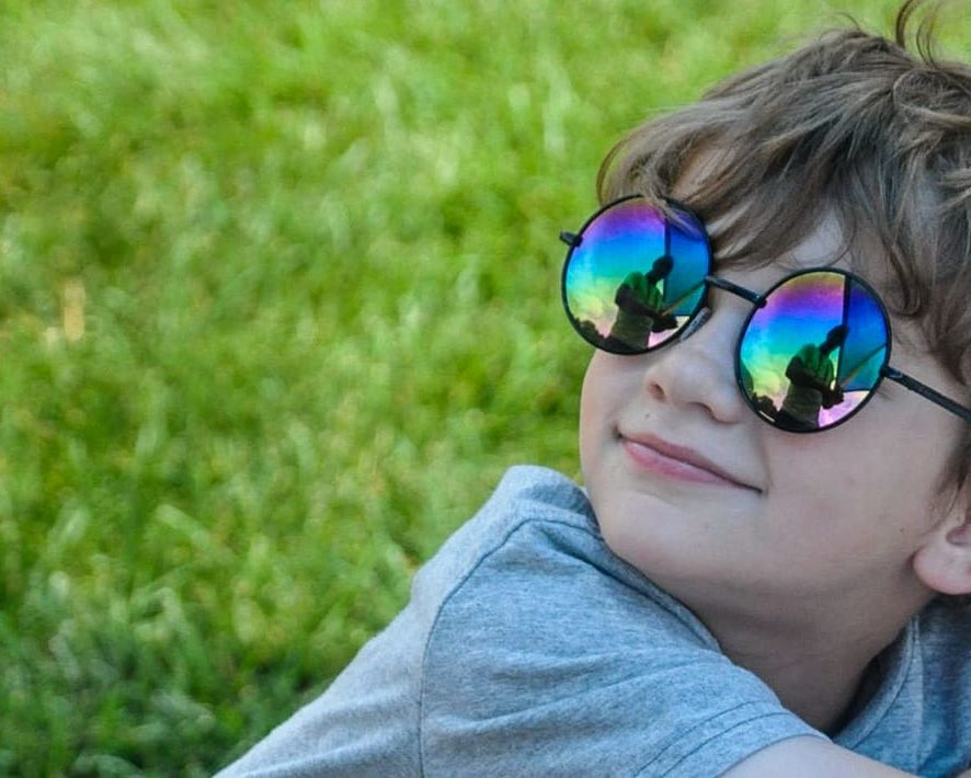 Young boy wearing sunglasses and sitting on the grass
