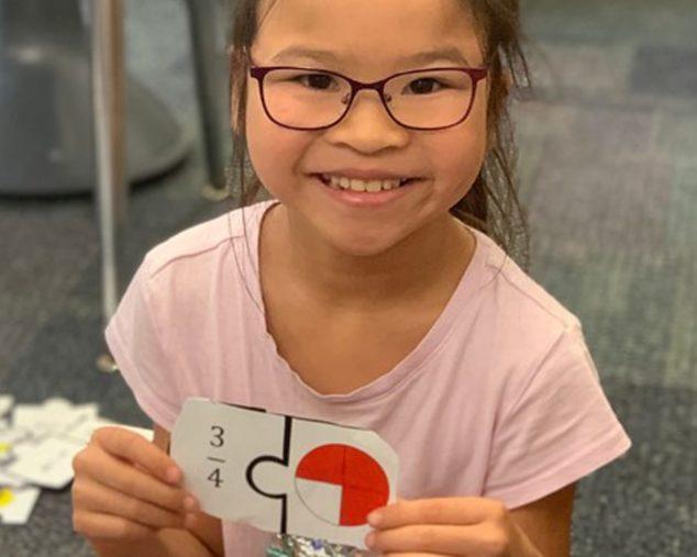 Young female holding ratio cards for algebra program