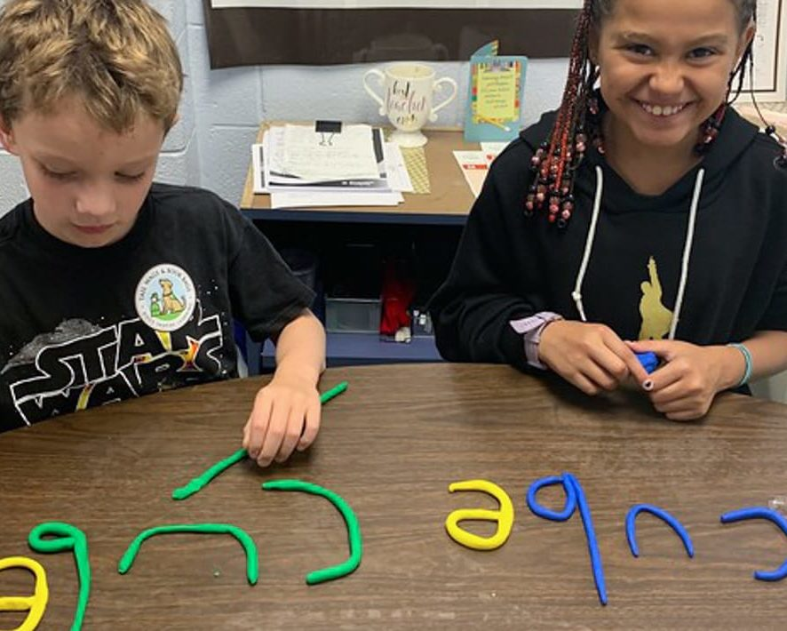Two students using clay letters to spell words