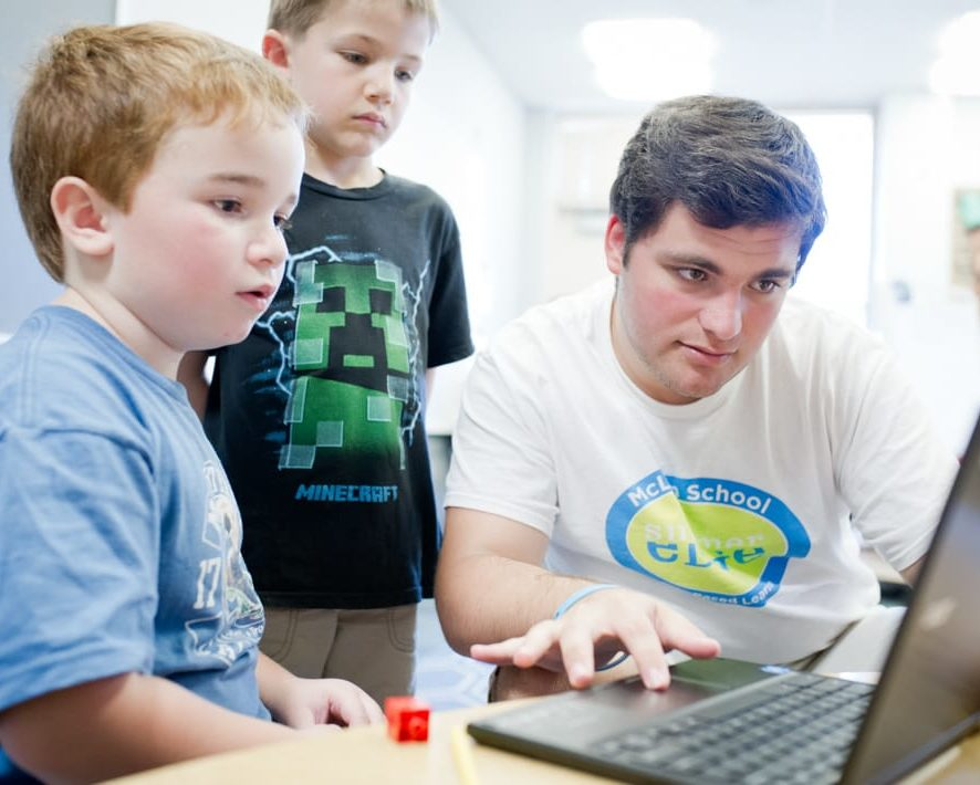 Staff and boys learning writing techniques on the computer