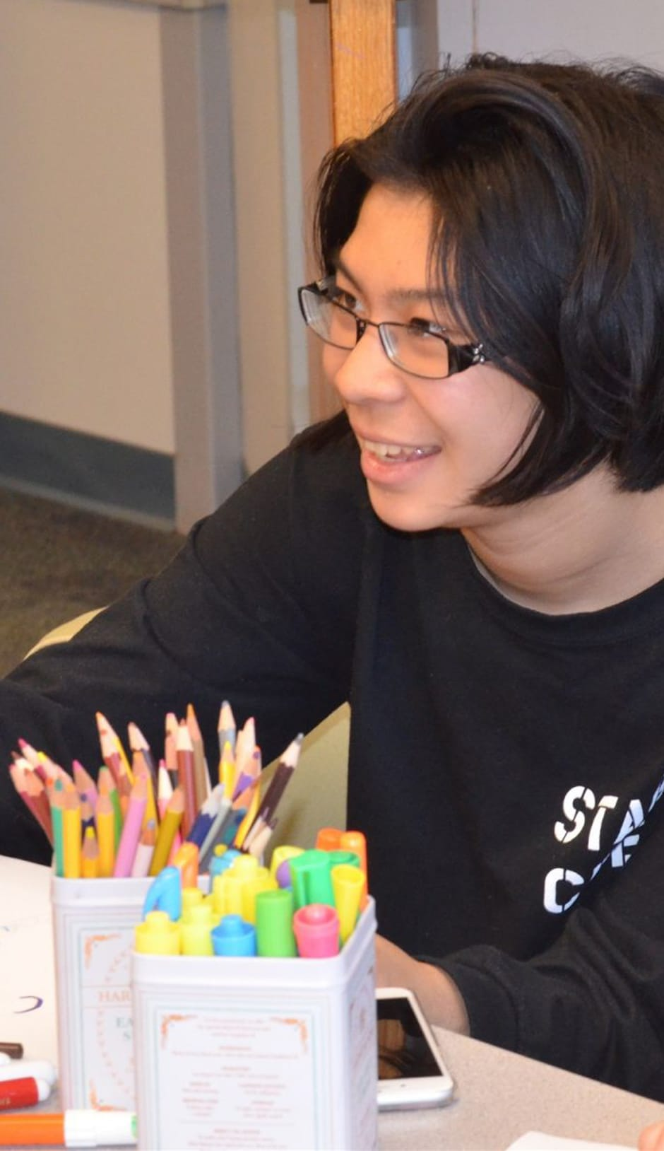 Student at Middle School Reading with colored pencils in front