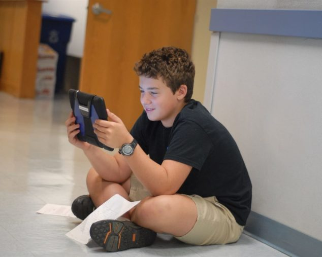 Middle school student in hallway practicing his writing