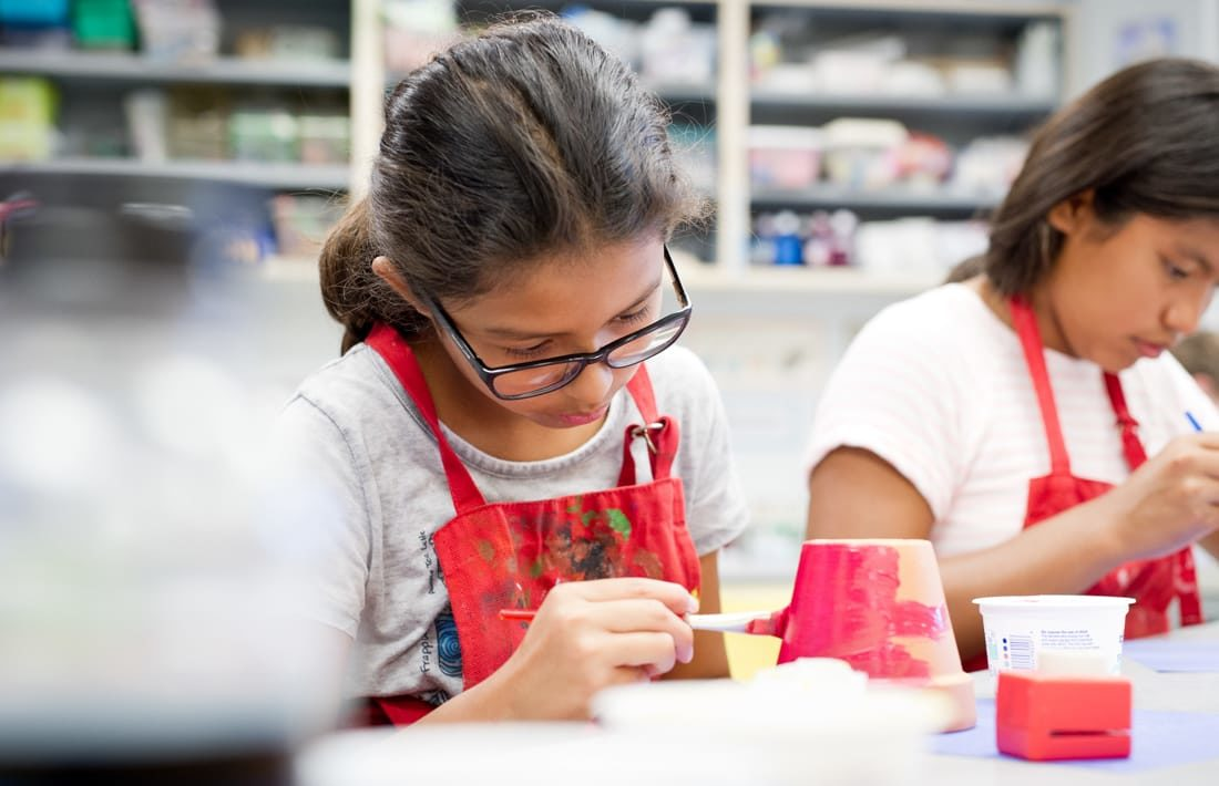 Two girls wearing red smocks and painting