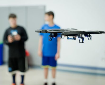 Two campers flying a drone in a classroom