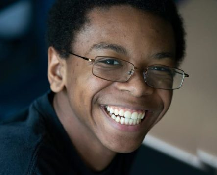 Male teen smiling and wearing glasses