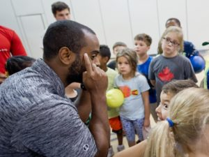 Adrien McDonald talking to kids in the gym
