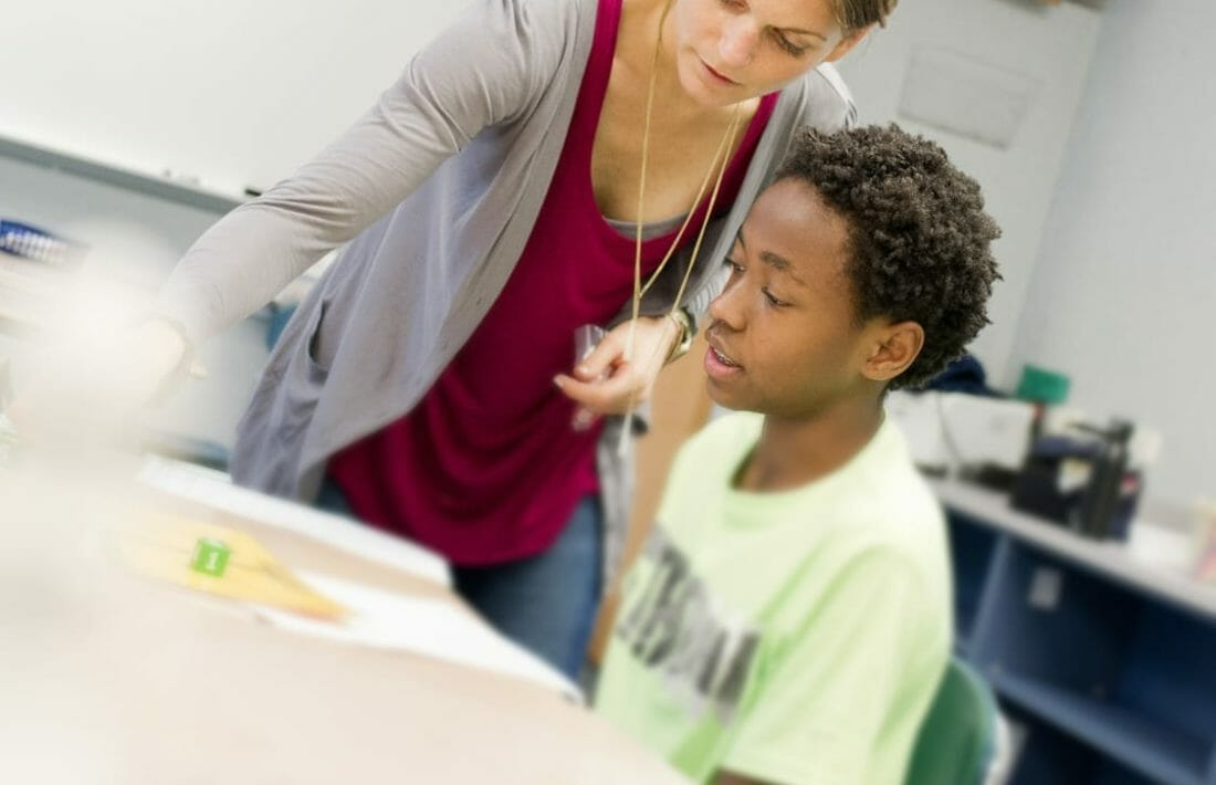 Student learning math with teacher's help