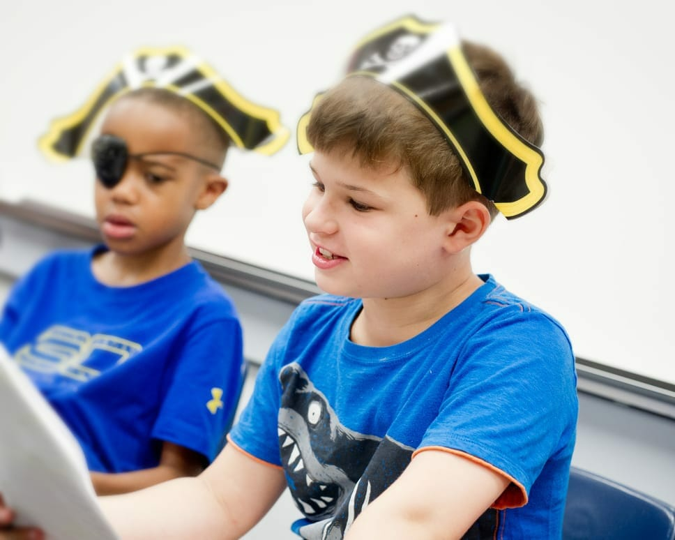 Two boys wearing pirate hats and eye patches reading