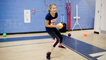 Girl throwing a dodgeball in the gym