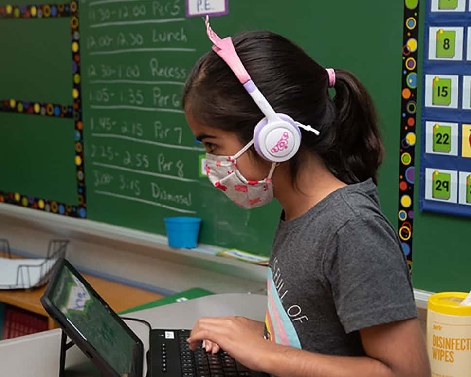 A student in a masking working on an assignment on her computer.