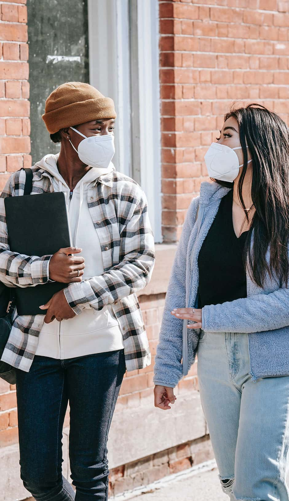Two students wearing maskings walking together.